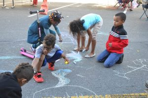 Kids draw with chalk on the street at Bronx Summer Fest 2016.